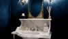 Shiny lacquered walls in dark blue with very decorative sconces create a formal powder bath.